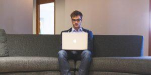 Man updating blogposts on laptop